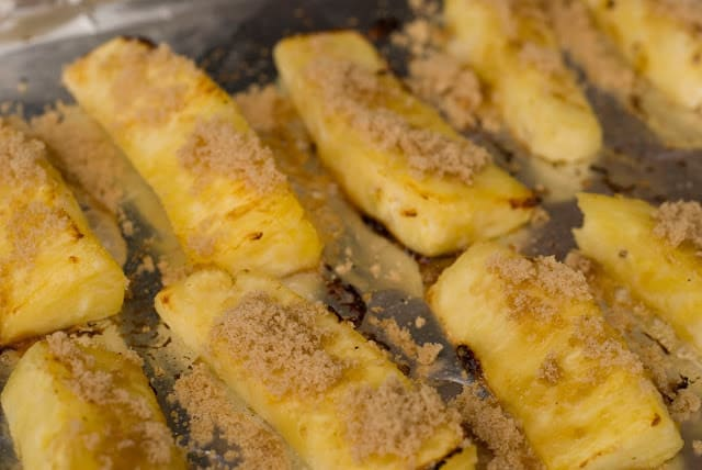 Grilling fresh pineapple slices sprinkled with coconut sugar