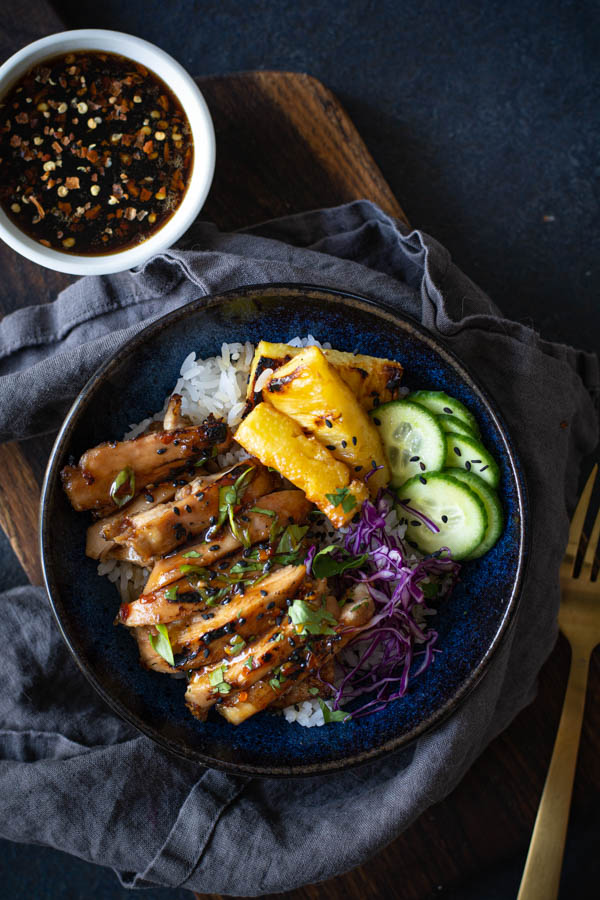 Blue bowl with rice topped with sliced coconut sticky chicken with grilled pineapple