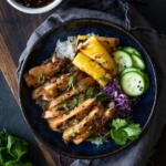 blue bowl on wooden board with white rice topped with sticky coconut chicken with grilled pineapple