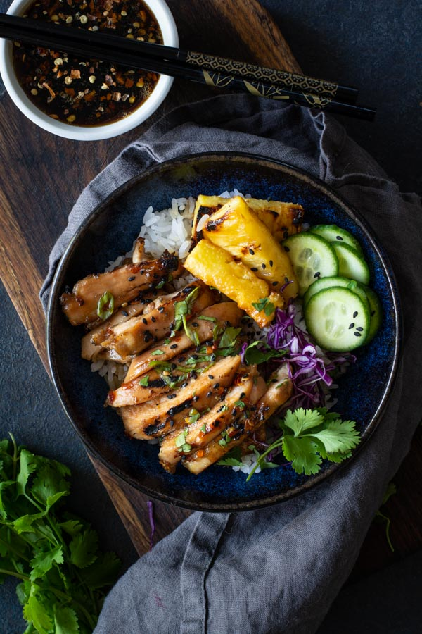 blue bowl on wooden board with white rice topped with coconut sticky chicken with grilled pineapple