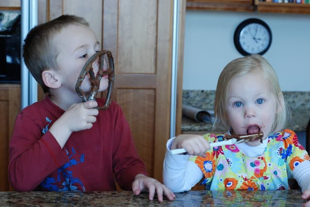 boy and girl licking chocolate cookie batter from beaters