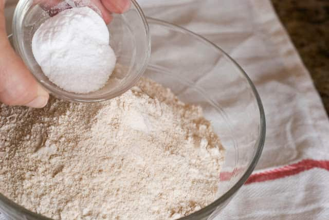 Wheat flour in bowl adding baking soda