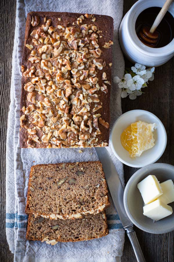Overhead shot of banana nut bread o linen cloth with honey and butter in bowls