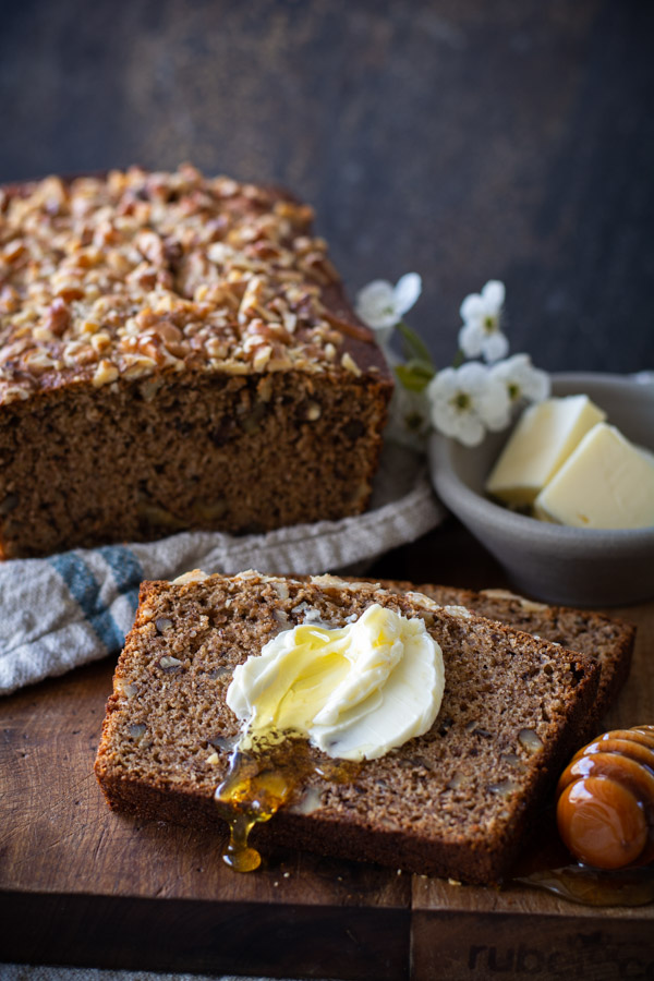 Slice of banana nut bread with spread butter and honey