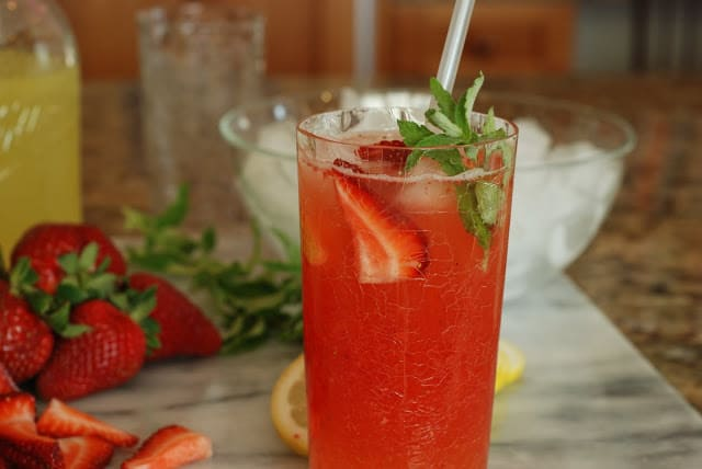 Tall glass of strawberry old fashioned lemonade with fresh strawberries and a sprig of mint