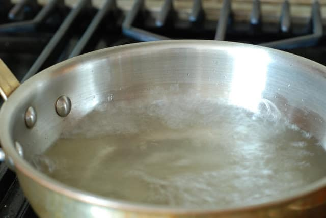 sugar and water boiling in a saucepan