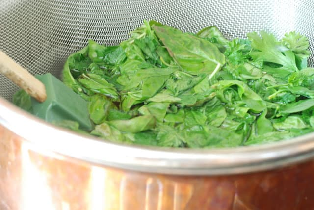 Strainer of fresh basil and parsley dropped in pot of boiling water