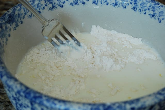 fork mixing in buttermilk into flour mixture