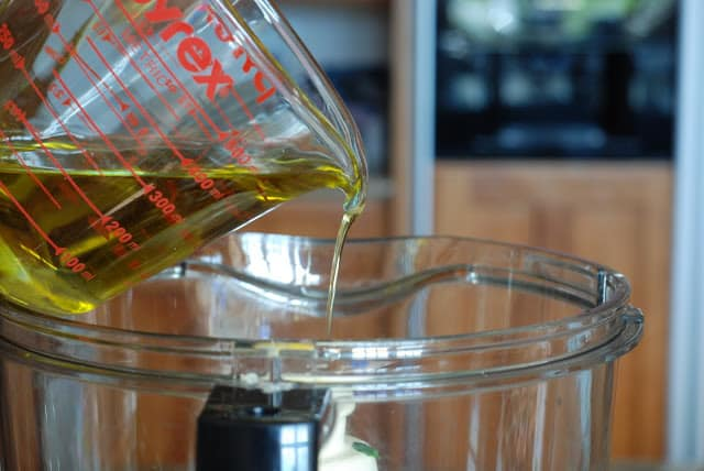 measuring cup of olive oil drizzled into food processor