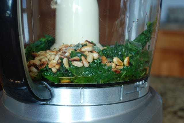 food processor bowl filled with blanched basil, pinenuts, olive oil