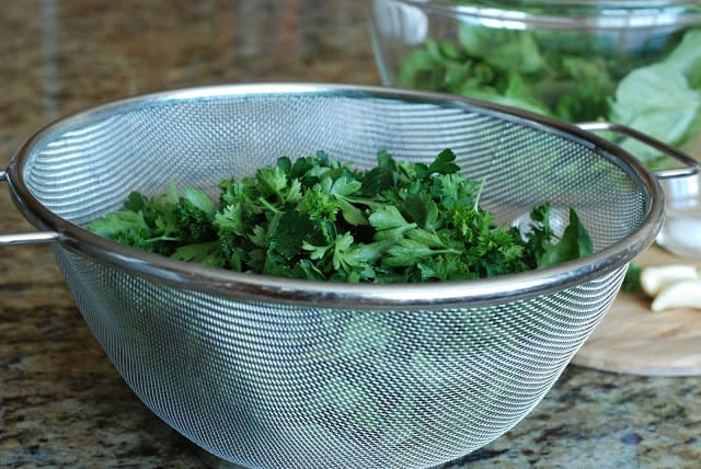 Wire mesh strainer filled with fresh basil and parsley
