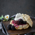 rustic blackberry shortcake on wood board with blackberries as garnish