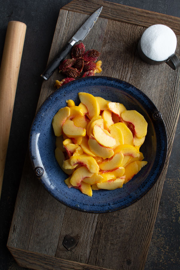 Large blue bowl with sliced peaches