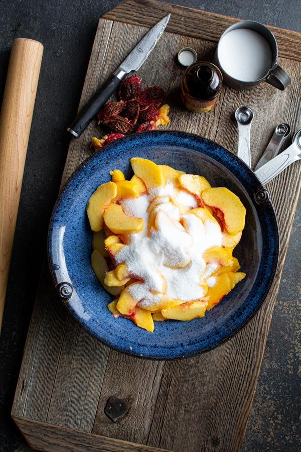 Blue bowl filled with sliced peaches with sugar on top