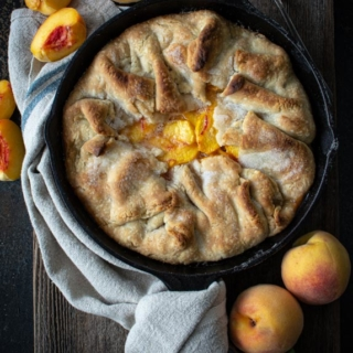 Baked southern peach cobbler in cast iron skillet