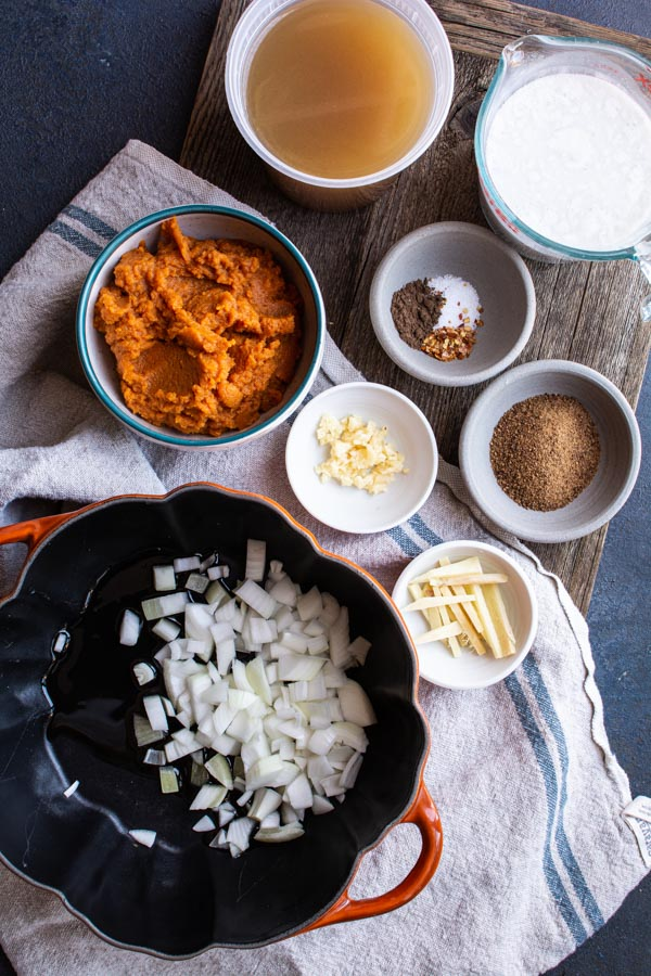 Pot with chopped onions surrounded by bowls of pumpkin and spices
