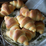 Baked crescent dinner rolls on a platter with linen cloth.