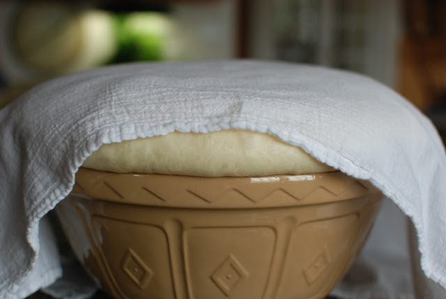 Bowl of risen dough covered with white cloth