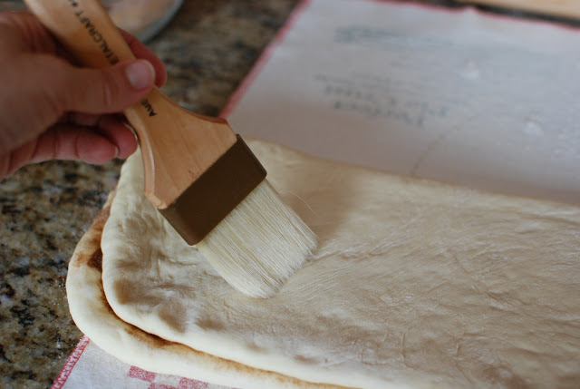 Dough folded over cinnamon sugar side. Pastry brush brushing off excess flour