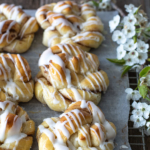 overhead shot of cinnamon twists on wood back drop with spring flowers on the side