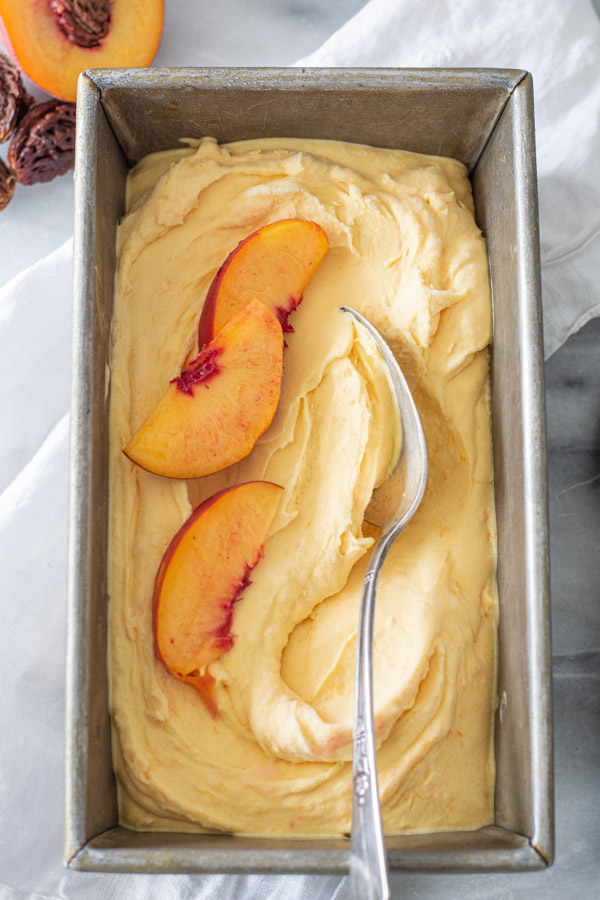 Overhead shot of peach ice cream in a metal pan with silver spoon