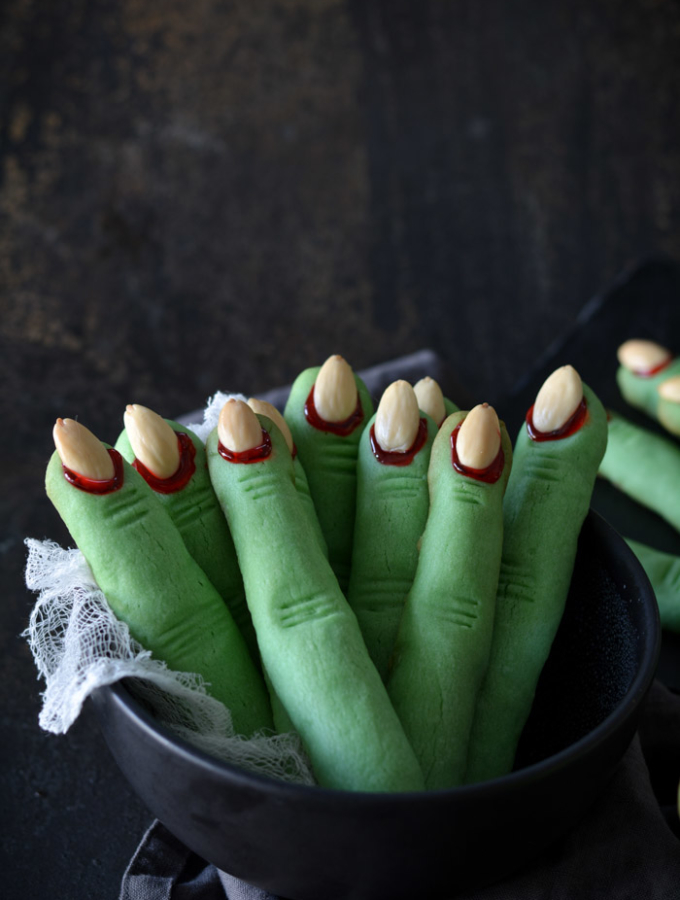 green Witch Finger Cookies standing in a black bowl