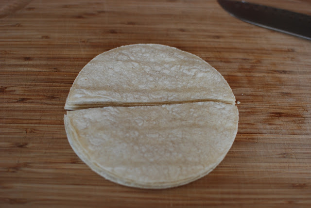 Corn tortillas cut in half on a cutting board