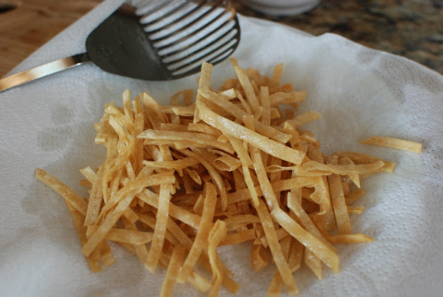 Fried tortilla strips on a paper towel lined plate