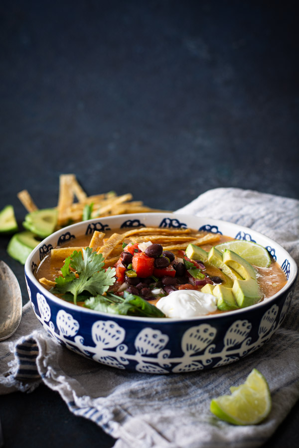 blue and white bowl with turkey tortilla soup with toppings