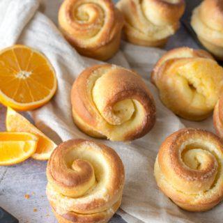 baked orange rolls on cloth with orange zest