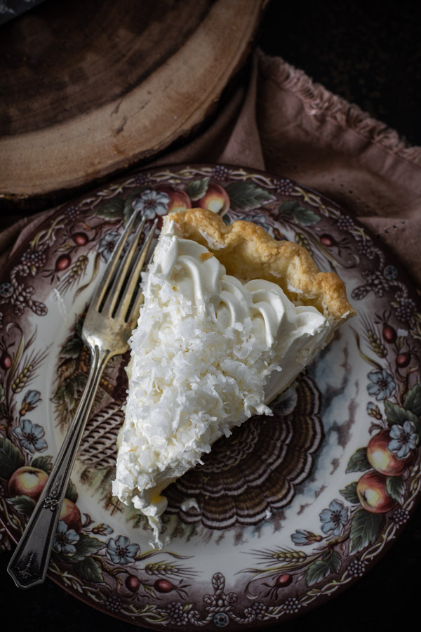 Over head shot of one slice coconut cream pie on a decorative plate