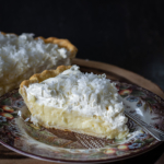 Side view of a slice of coconut cream pie with whole pie in back ground