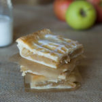 Slab Apple Pie squares stack between waxed paper