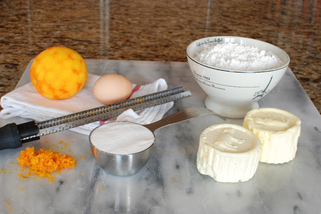 Butter, orange, egg, sugar, flour on marble board