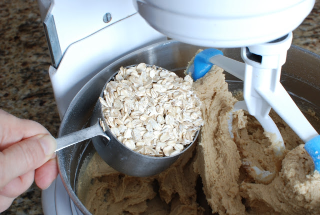 Scoop of oatmeal added to mixing bowl
