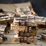 Stacked peanut butter bars with chocolate drizzle