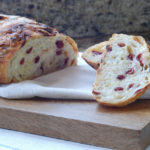 sliced orange cranberry bread on cutting board with 2 slices