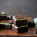 Two stacked chocolate mint brownies on a wooden cutting board