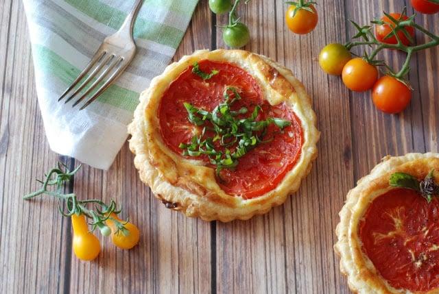 small round tomato tart with basil garnish