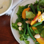 peaches, green beans, almonds, greens, and ricotta on white plate