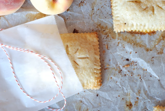 hand peach pie in a glassine bag on baking sheet with red and white twine