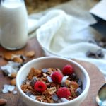 Chocolate granola in a bowl with fresh raspberries