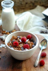 bowl of granola with fresh raspberries, spoon and milk