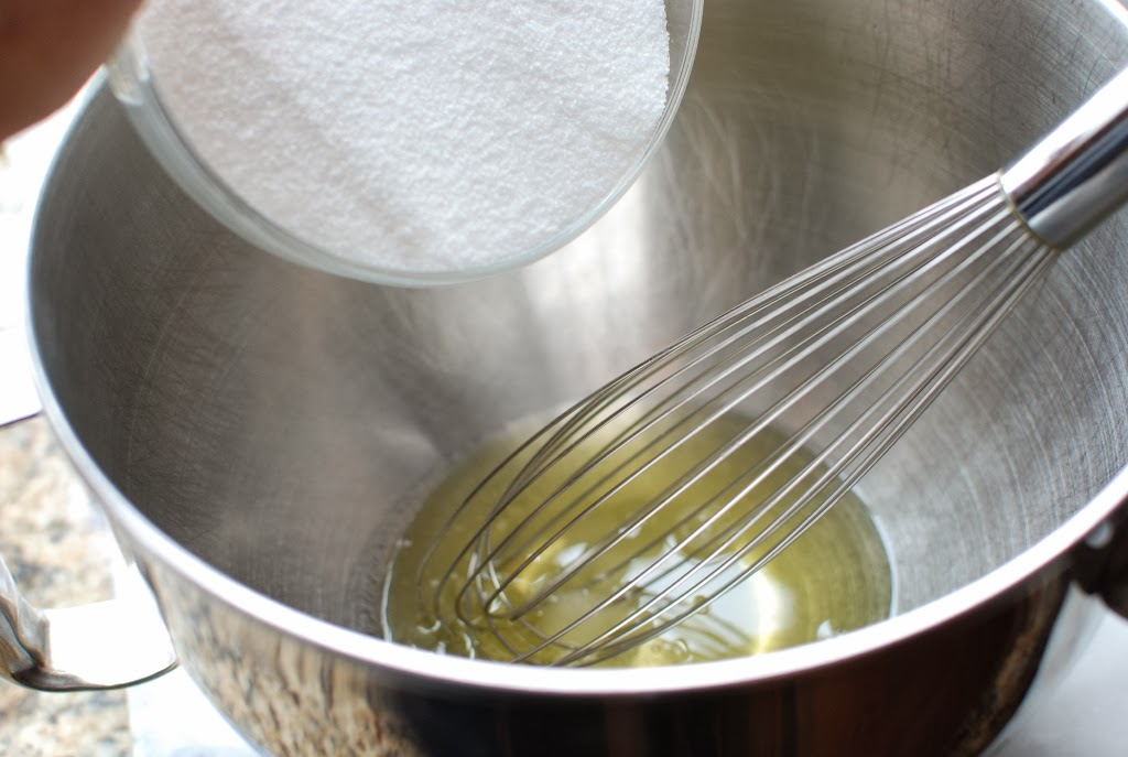 egg whites with sugar pouring into bowl and wire whisk