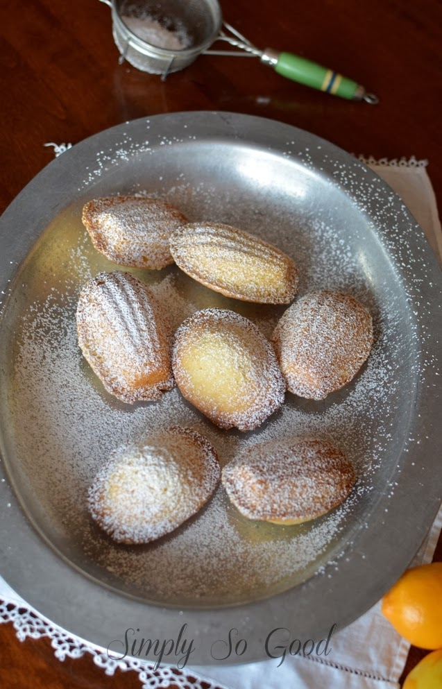 Madeleines on a metal plate sprinkled with powdered sugar