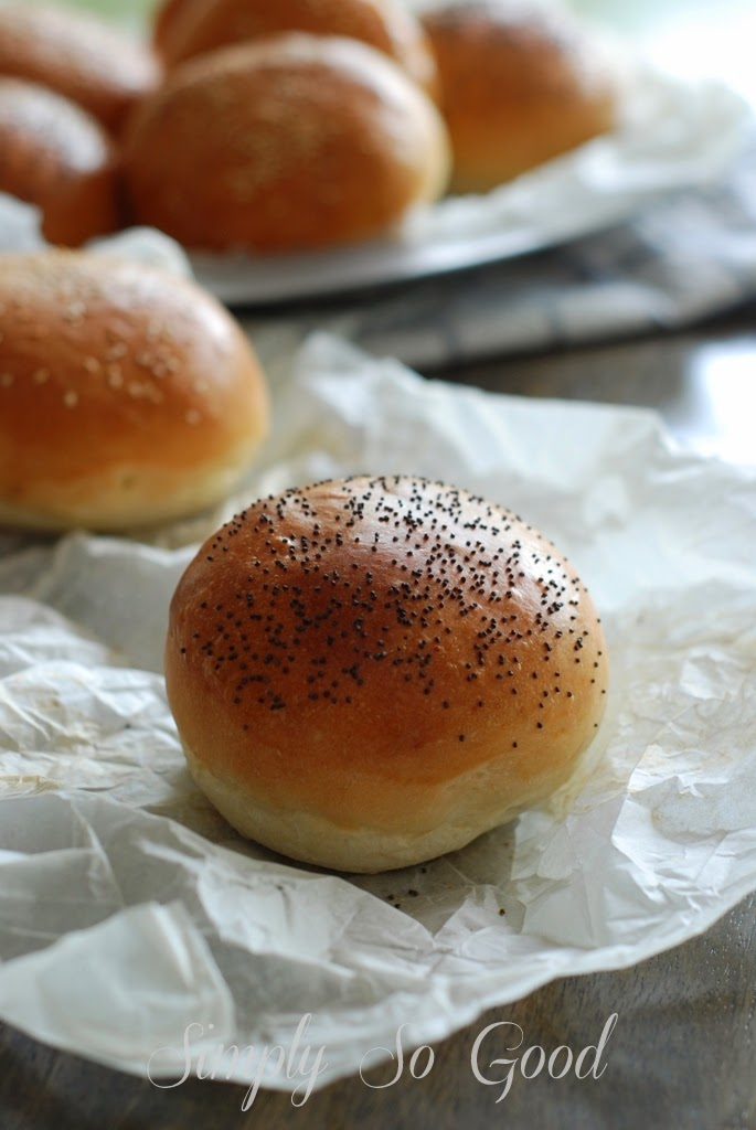 Brioche burger buns sprinkled with poppy seeds on sheet of parchment