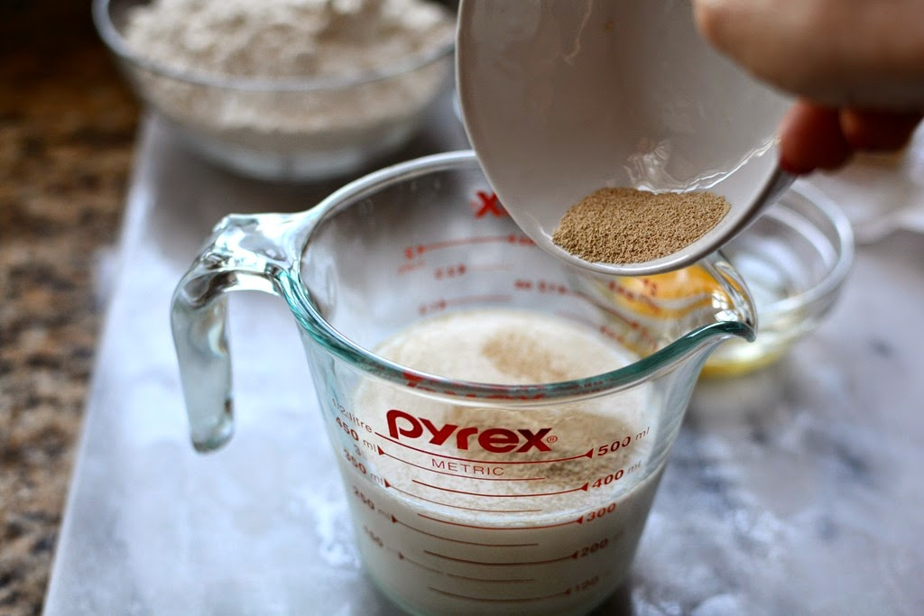 yeast being added to milk in measuring cup