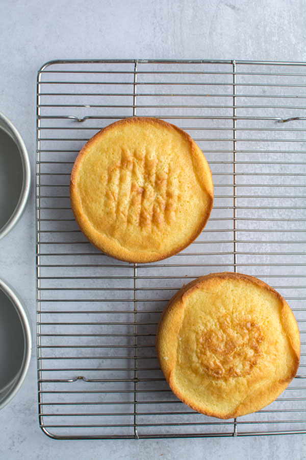two round cakes on cooling rack