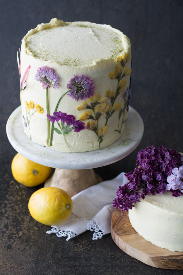lemons by a lemon olive oil cake with pressed flowers
