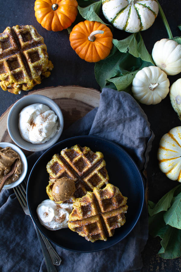 Pumpkin Waffles on black plate surrounded by small pumpkins